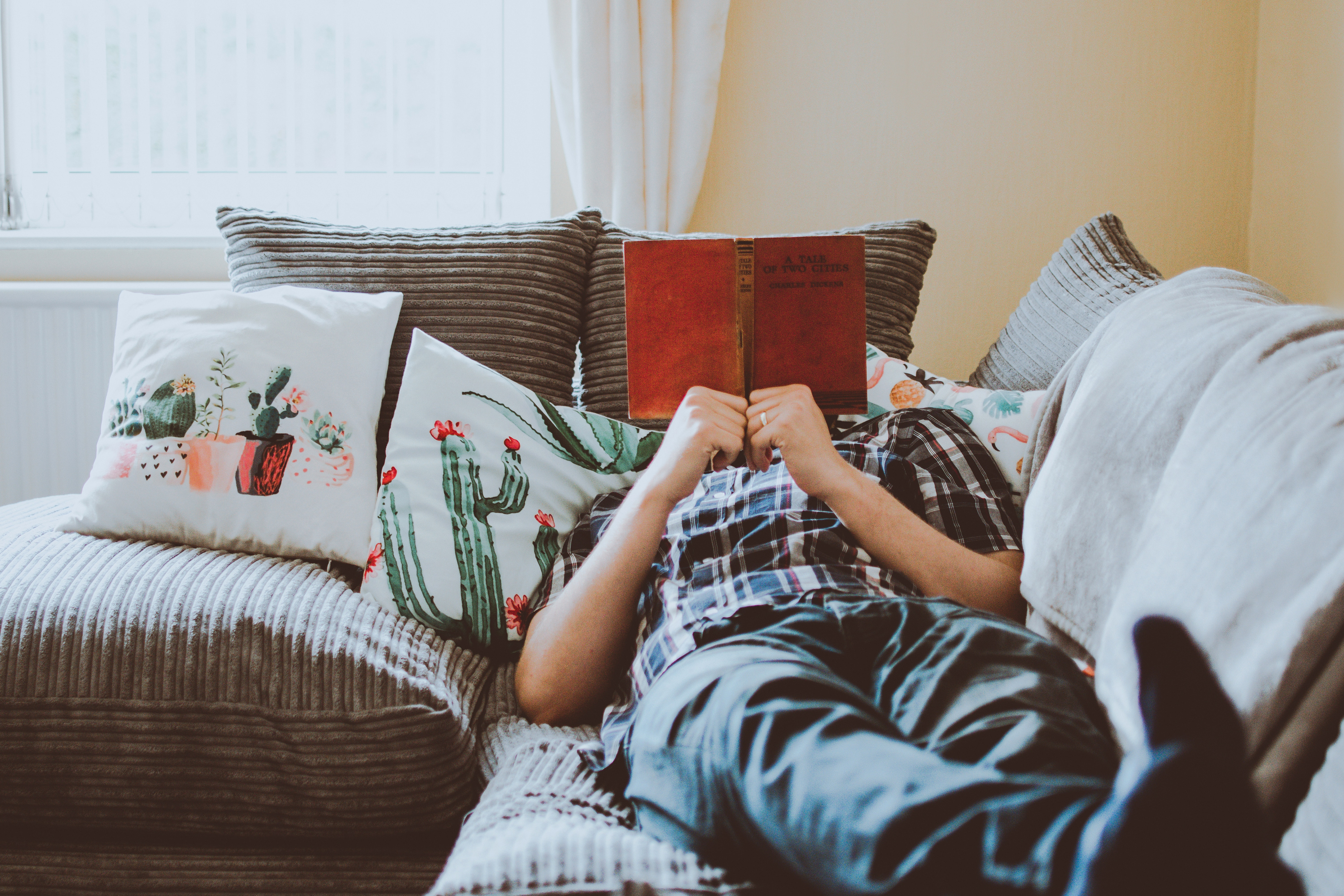 someone laying on a couch reading a book