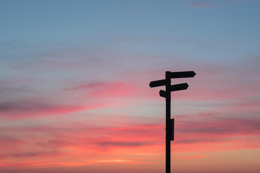 silhouette of road sign against blue and pink sky