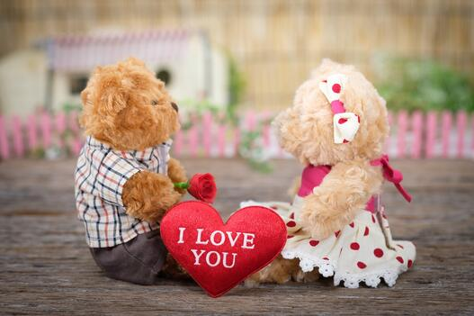 Two teddy bears with a heart that says 'I love you'