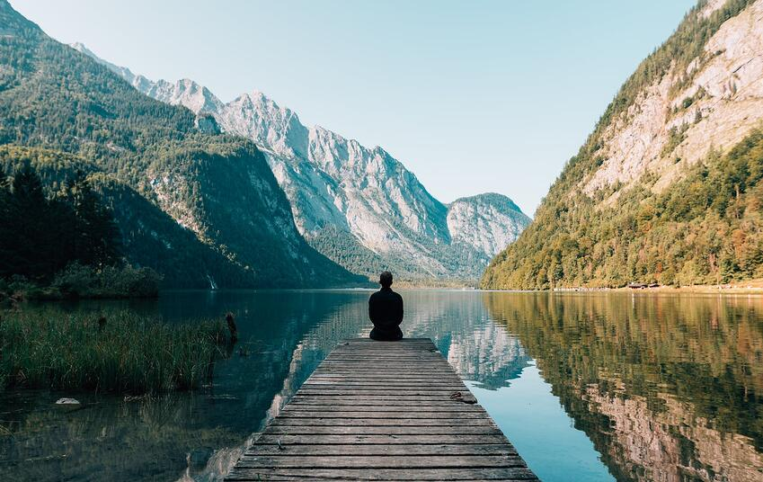 Person sitting on the end of a dock in front of a mountain scape