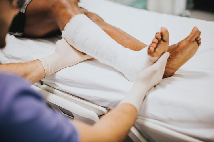Nurse assisting man with bandaged leg