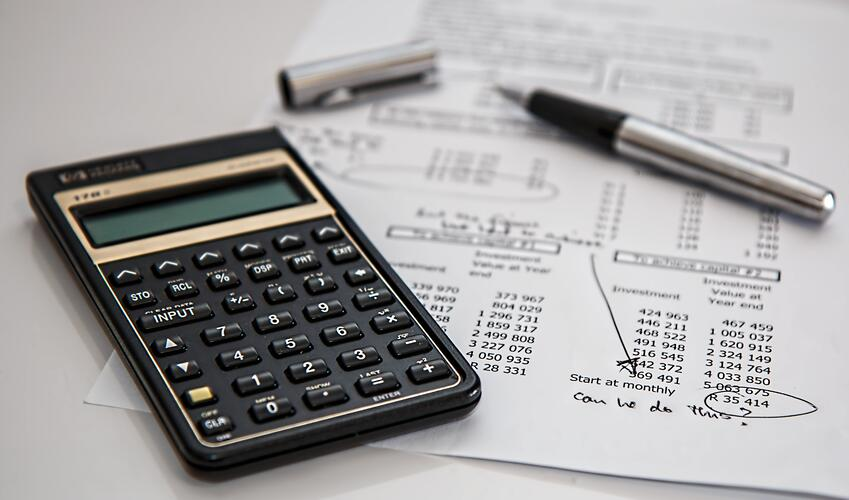 calculator and expense sheet on table