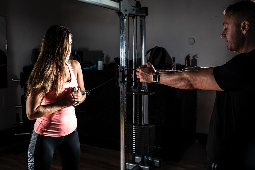 trainer helping girl with fitness machine