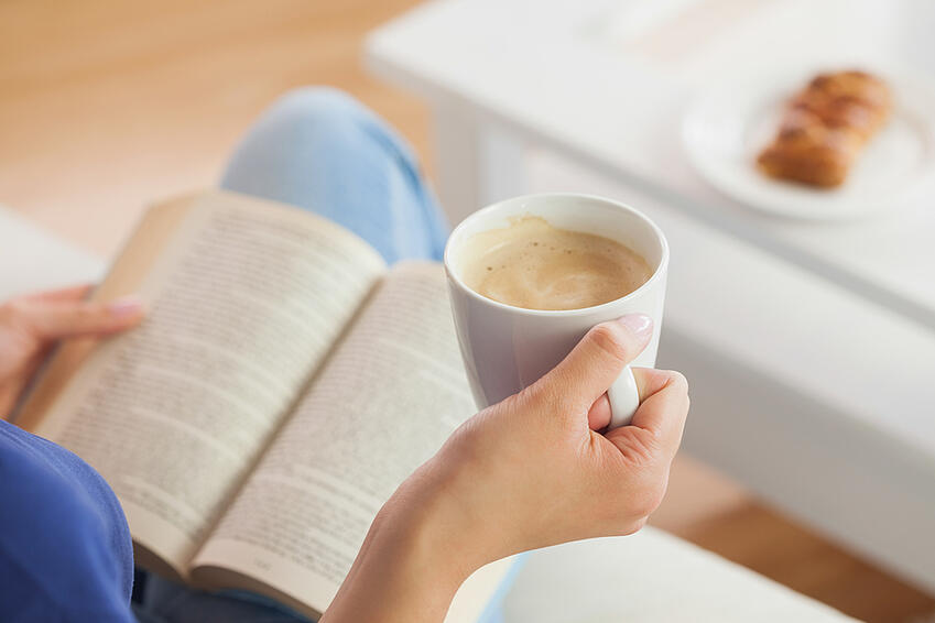 Woman sitting on the sofa reading a book holding her coffee mug in living room at home.