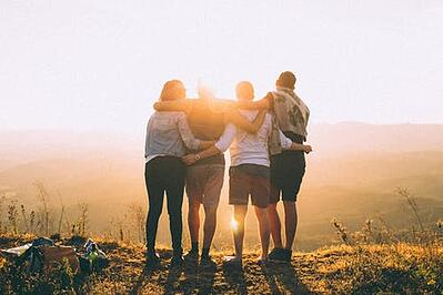 four people embracing while watching the sun set