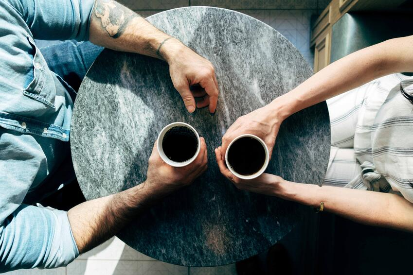 Two people drinking coffee at a table
