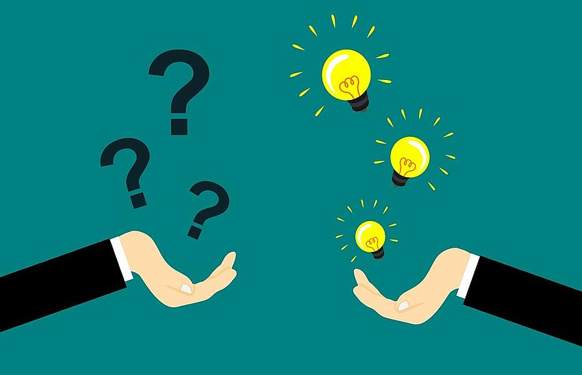 one hand holding question marks and one hand holding light bulbs